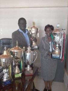 MR NASONGO AND MRS NABISWA DISPLAY THE FIVE CHOIR NATIONAL TROPHIES WON IN 2017